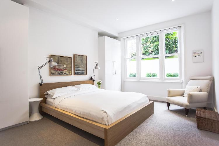 bedroom looking out to foliage and blooms within London Brechin Place III luxury apartment