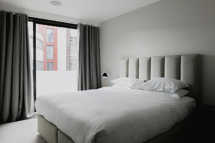 snug bedroom with a glass door to the balcony of London Compton Street luxury apartment