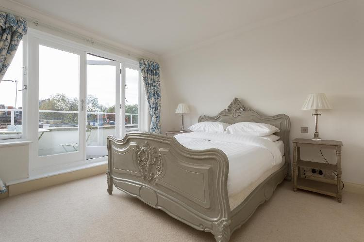 beautiful bedroom with balcony in charming and cheery London Cale Street luxury apartment