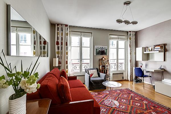 living room with a desk beside the bright windows, and red sofa bed in paris luxury apartment