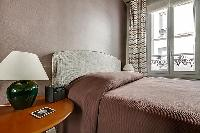a queen-size bed with wooden bedside table, and a stylish lamp in paris luxury apartment
