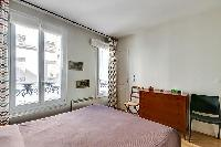 master bedroom with bright windows, a queen-size bed, a wooden closet and two seats in paris luxury