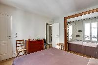 bedroom with a large wooden wardrobe closet with a full-length mirror placed beside the bed in paris