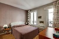 master bedroom with a queen-size bed and wooden floor in paris luxury apartment