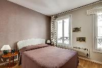 master bederoom with a queen-size bed in paris luxury apartment