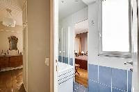 blue-tiled bathroom furnished with a shower area, a sink, a mirror, and a hairdryer with access to t