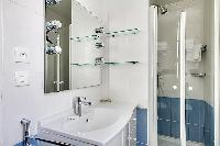 blue-tiled bathroom furnished with a shower area, a sink, a mirror, and a hairdryer in paris luxury