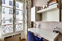 a desk with blue chair, a telephone, and selection of books beside the window in paris luxury apartm
