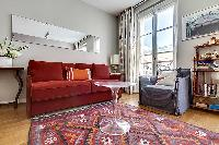 living area with red sofa bed and ghost round center table in paris luxury apartment