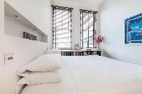 pristine bedroom with tall windows in London Airlie Gardens IV luxury apartment