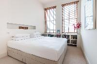 crisp linens of the large bed in London Airlie Gardens IV luxury apartment