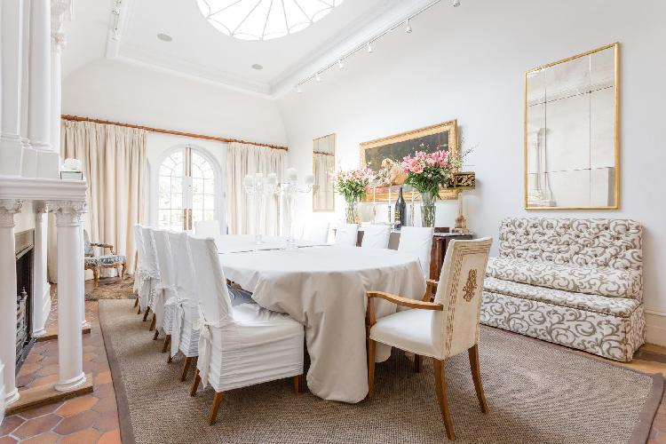 skylight-illuminated dining room with exquisite furniture and fancy arch door in London Cheyne Walk