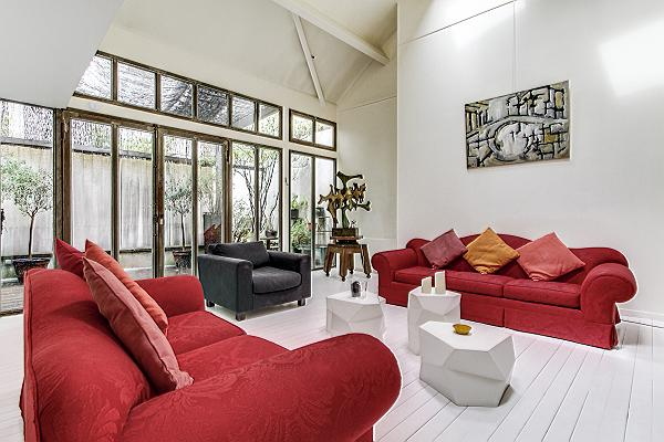 living area with high ceilings, two red sofas, a set of artistic center tables, a chair, and a large