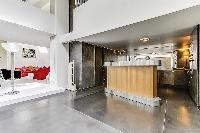 fully equipped kitchen with grey tiles and built-in wooden cabinets in a 2-bedroom loft Paris luxury