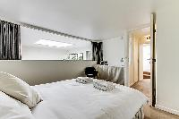 master bedroom with a queen-size bed, bedside tables with lamps, built-in closets, and a chair in a