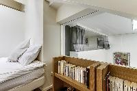 second bedroom on the mezzanine level with two single beds that can be converted into a queen-size b