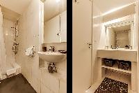 An en-suite bathroom with a shower area, sink, and toilet in a 2-bedroom loft Paris luxury apartment