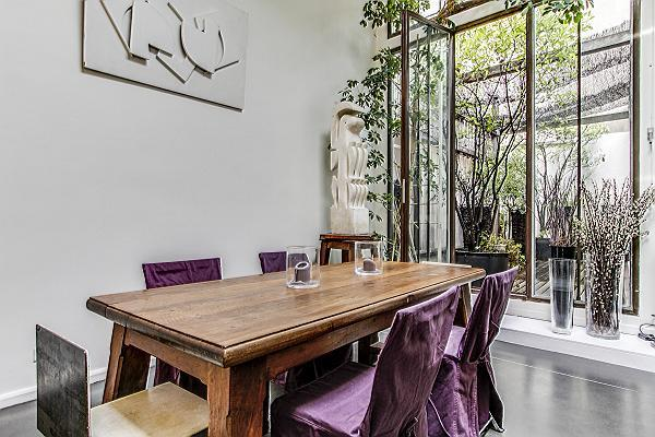 elegant dining area with wooden table and six chairs in a 2-bedroom loft Paris luxury apartment
