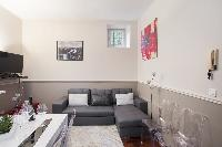 open-plan living area with a gray sofa bed, gray and white cushions, a TV, stylish lamps, white dini