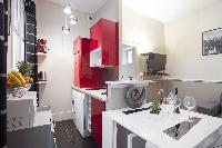 equipped kitchen in red and white hues and white dining table in a 1-bedroom Paris luxury apartment