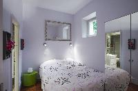 chic bedroom with a double bed and a closet with door mirrors in a Paris luxury apartment