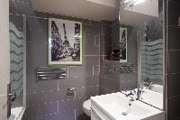 modern bathroom with gray tiles, a bathtub with integrated shower, and a toilet in a Paris luxury ap