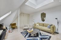 cozy living area with comfortable sofas, full of closets, and white painted eaves walls in Paris lux