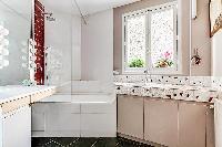 sleek bathroom with a bathtub, shower, and sink in a Paris luxury apartment