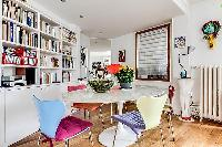 colorfully designed dining area for 4 with bookshelves in a Paris luxury apartment
