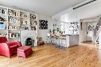 fully equipped open kitchen and living area with red chair, bookshelves, and fireplace in a Paris lu