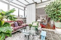 a sunroom, a unique feature, made of glass windows and green vegetation in a Paris luxury apartment