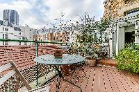 outdoor terrace with views of Parisian rooftops in a Paris luxury apartment