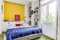 first bedroom with queen size bed, bright yellow wall, and book shelves in a Paris luxury apartment