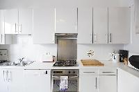 immaculate white fully-equipped kitchen in a 3-bedroom Paris luxury apartment