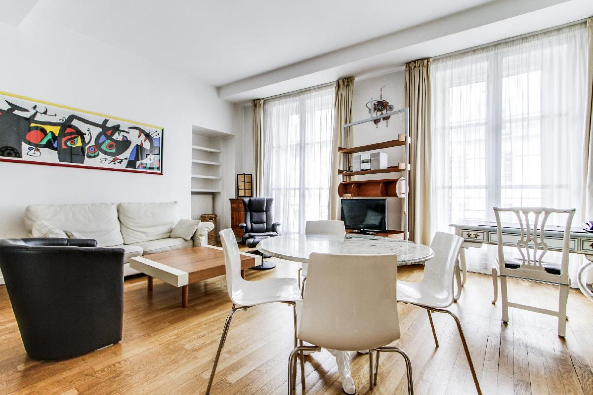 lovely dining area with white round table and 4 chairs in a 2-bedroom Paris luxury apartment