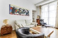 spacious living area with double-glazed windows, sofa, armchairs, paintings, shelves, nightstand, an