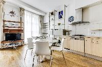 lovely dining area, multimedia cabinet and kitchen in a 2-bedroom Paris luxury apartment