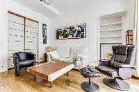 spacious living area with wooden floor, sofa, armchairs, reclining chair, and shelves in a 2-bedroom