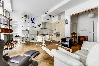 spacious living area with wooden floor, a tv, sofa, 2 armchairs, dining area, and kitchen in a 2-bed