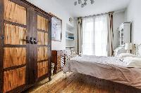 first bedroom with a queen size bed, rustic cabinet, shelves, nightstand, and lamp in a 2-bedroom Pa