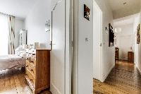 first bedroom and hallway with rustic interiors in a 2-bedroom Paris luxury apartment