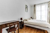 second bedroom with 2 single beds, desk and chair in a 2-bedroom Paris luxury apartment