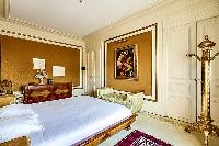 master suite intricately decorated and furnished with a king-size bed, a sofa, chairs, a mirror, and