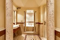 an elegant marble en-suite bathroom with a bathtub, a detachable shower head, a sink, a mirror, and