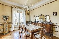 dining area with elegant gold pieces and an intricate wooden dining table or 6 in a 3-bedroom Paris