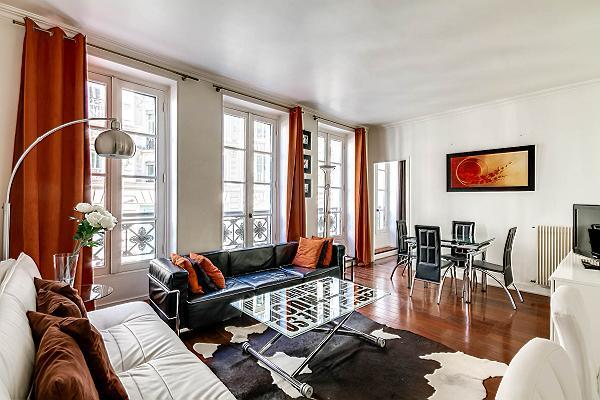 sunny living room with two sofas, center table, and three large French windows in a 2-bedroom Paris