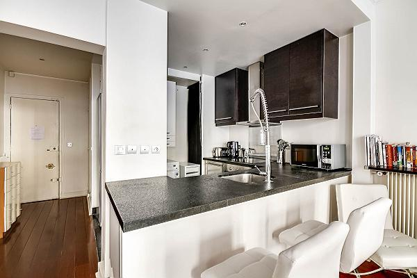 modern and space-efficient kitchen with breakfat bar and stools in a 2-bedroom Paris luxury apartmen