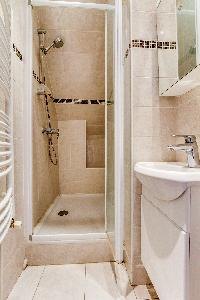 white and beige-tiled bathroom with shower and sink in a 2-bederoom Paris apartment