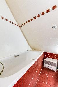 red-tiled bathroom with bathtub in a 2-bedroom Paris apartment