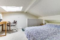 brand-new queen-size bed in the bedroom with sofa and study table beneath a skylight